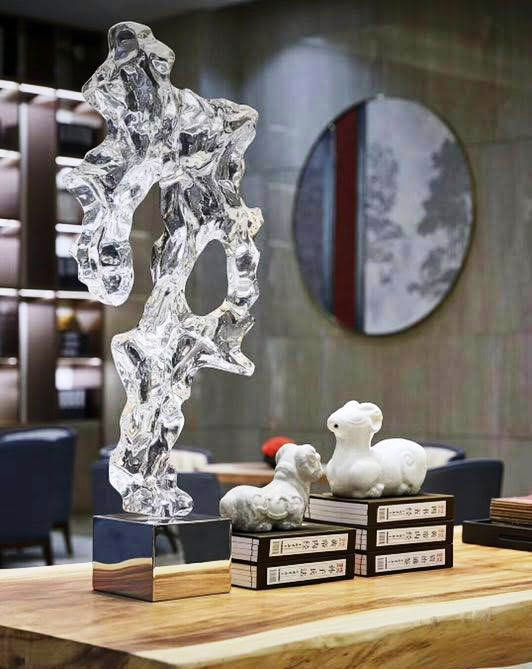 oriental casa - five home decor refresh tips for spring resin decor - A sculpture sits on a desk with Chinese objects.